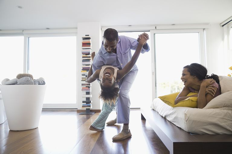 Cheerful father and daughter dancing in bedroom