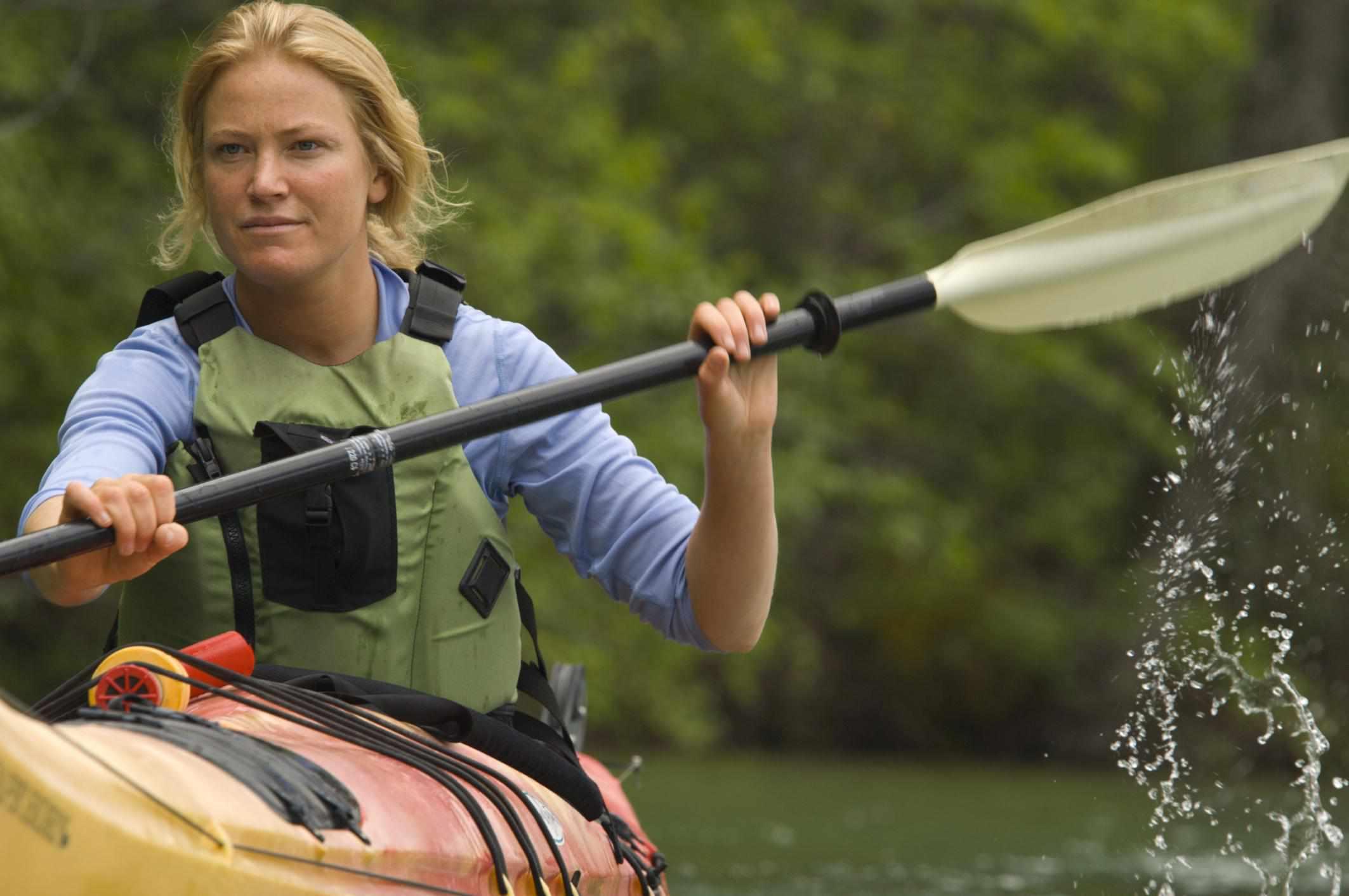 Woman sea kayaking on lush lake