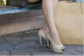 Woman seated in peep-toed pumps.