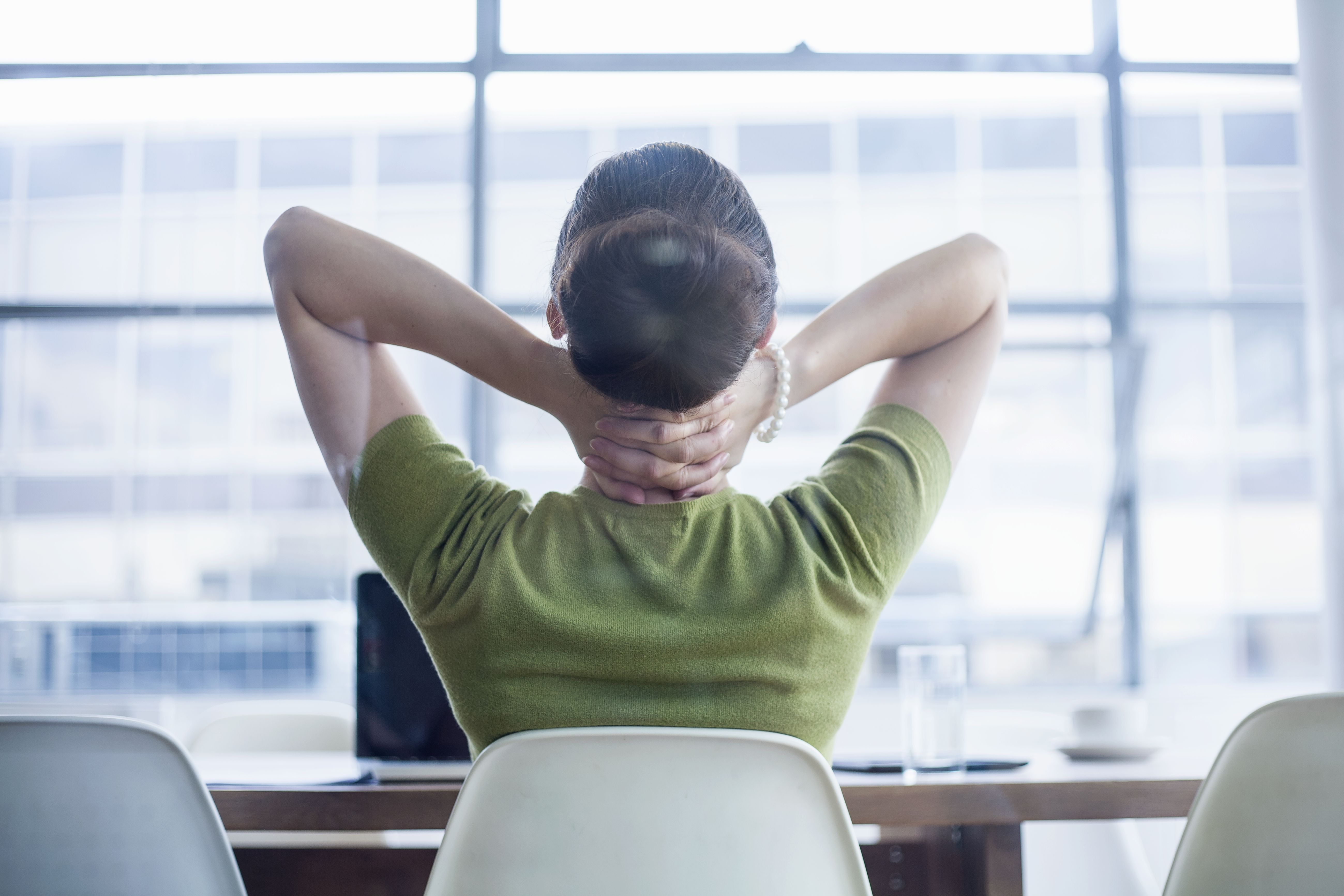Young woman stretching at desk
