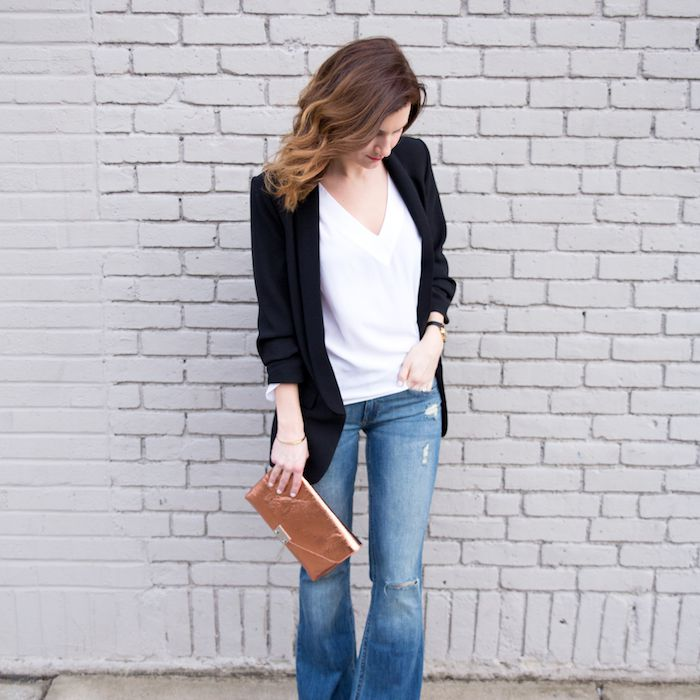 Woman in classic outfit of jeans and t-shirt and black blazer