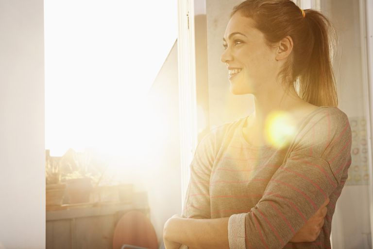 Portrait of happy woman standing at open window