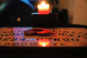 Heart shaped planchette on Ouija board by a candle in a dark room