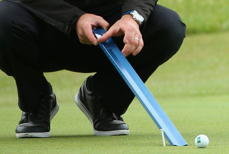 Tournament official rolls golf ball down Stimpmeter to measure the green speeds