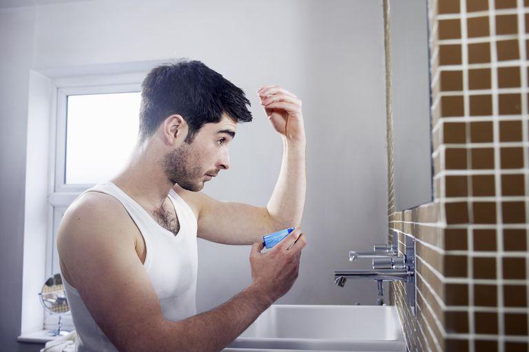 Man applying gel to hair in bathroom