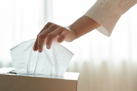 Woman's hand picking tissue from the tissue box