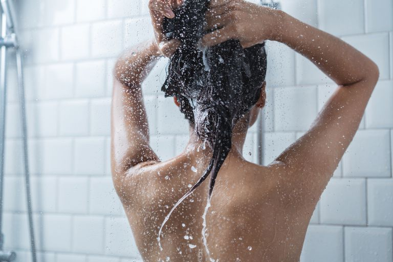 View from behind of woman washing her hair in the shower