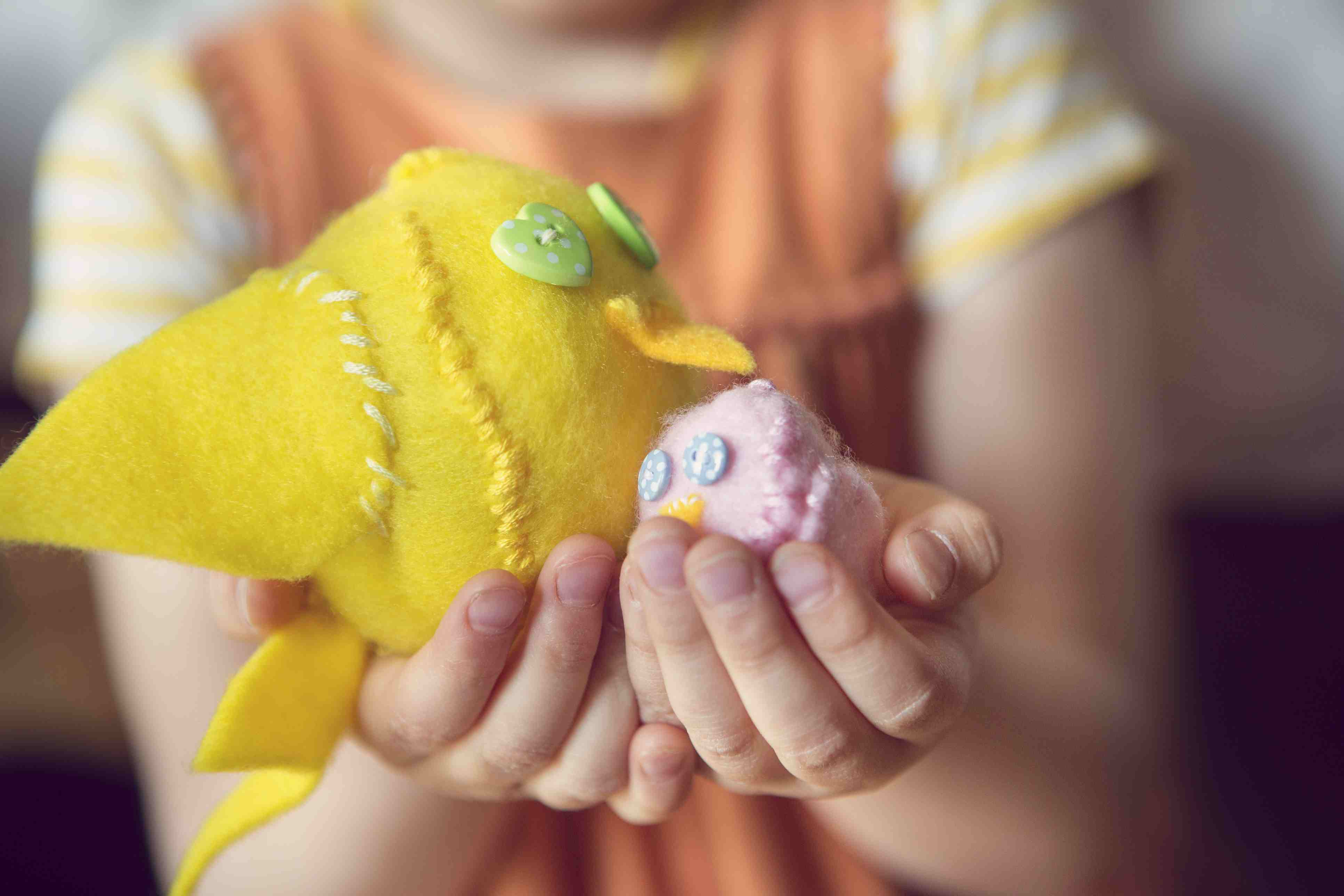 Child holding homemade felt chicks