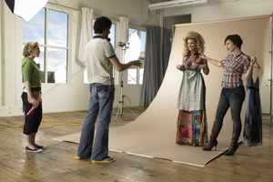 Stylists, model and photographer discussing wardrobe on set