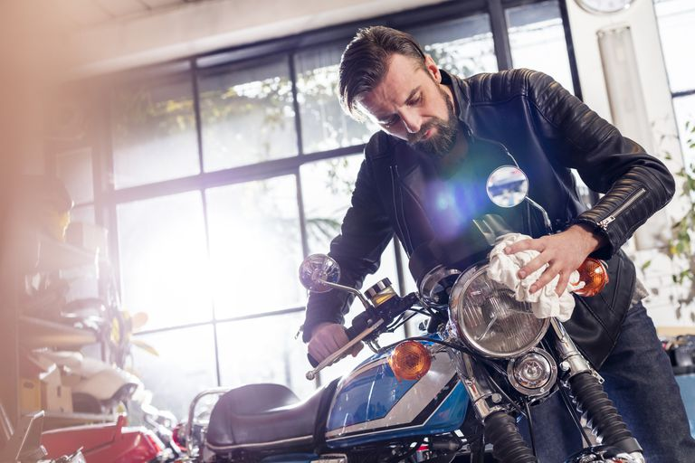 Male motorcycle mechanic wiping motorcycle in workshop