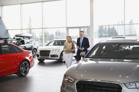 woman and man walking around car dealership