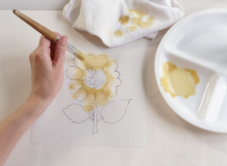Hand blotting pale yellow paint onto petals of sunflower stencil, painting white fabric below, using wooden-handled paint brush.