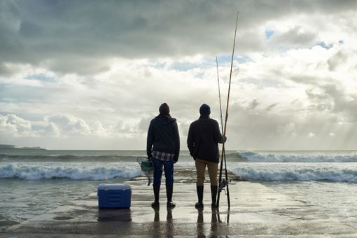 Shot of two young men fishing at the ocean in the early morning