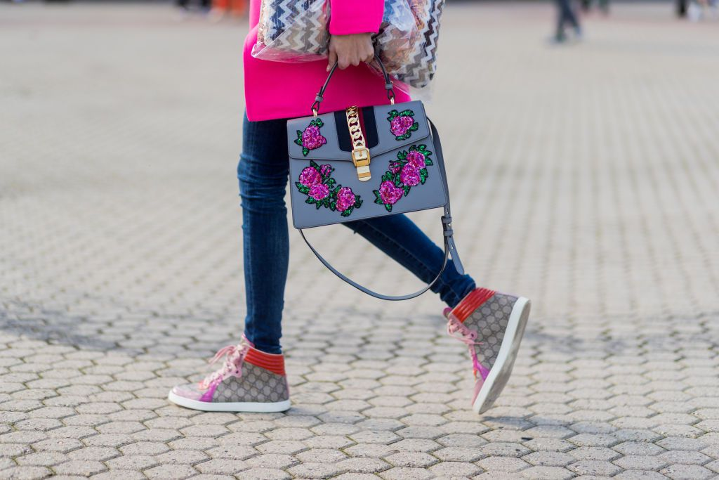 Woman wearing jeans Gucci sneakers and Gucci purse
