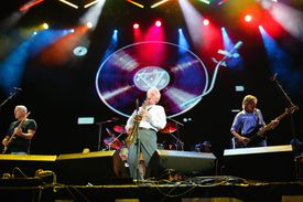 Pink Floyd performing onstage against album light show.