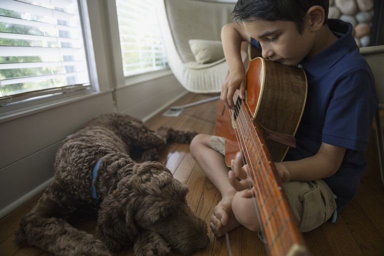 boy playing guitar with his dog
