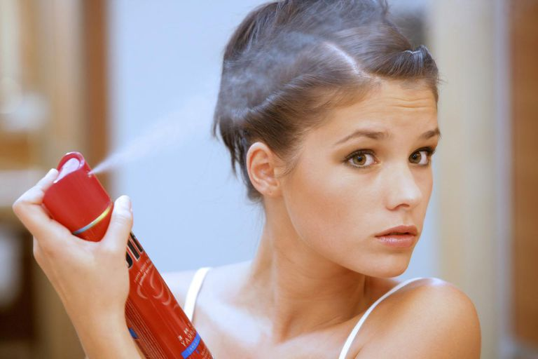 Young woman using hairspray