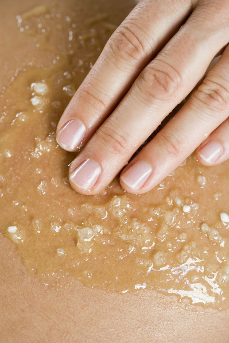 a woman's hand touching skin covered in sugar scrub