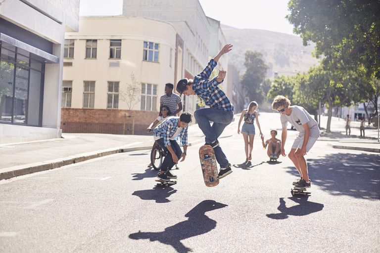 Teenage friends skateboarding on sunny urban street