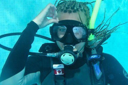 A scuba diver allows water to enter her diving mask.