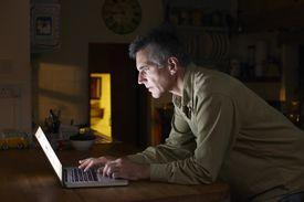 Man using laptop in kitchen at night