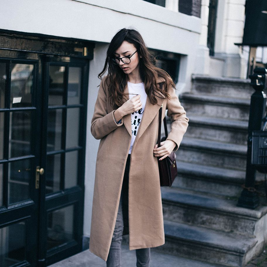 Womna in camel coat and grey jeans