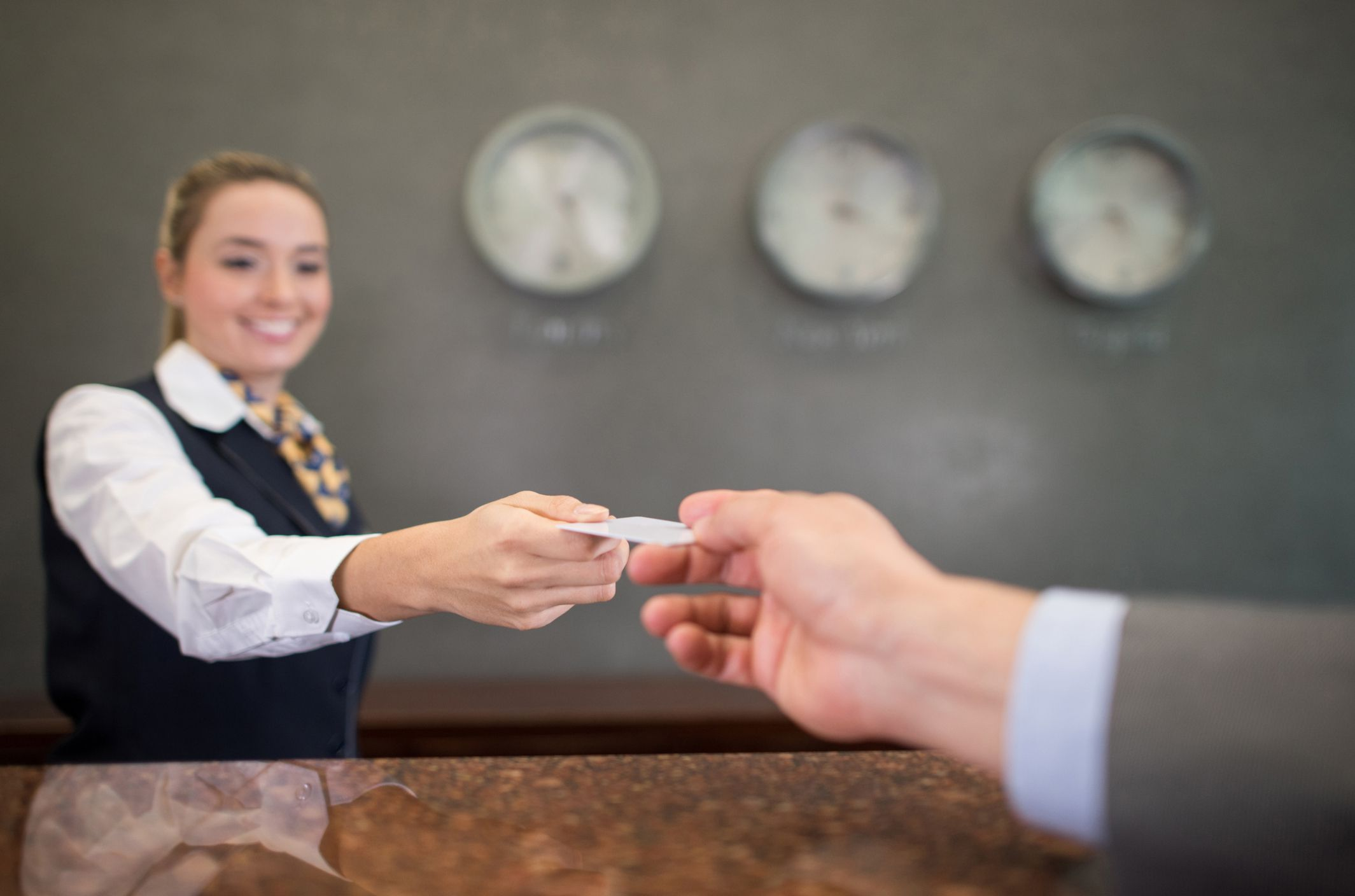 A woman working at a hotel handing over a loyalty card to a customer