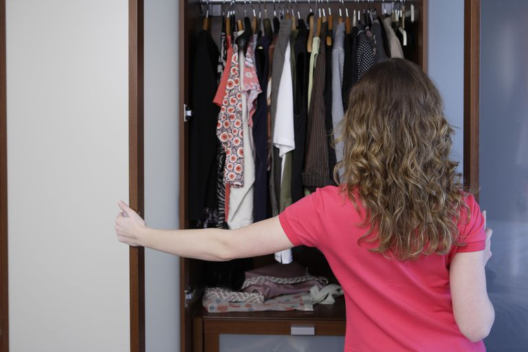 Young woman facing open wardrobe, rear view