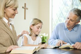 Family Reading Bibles at Table
