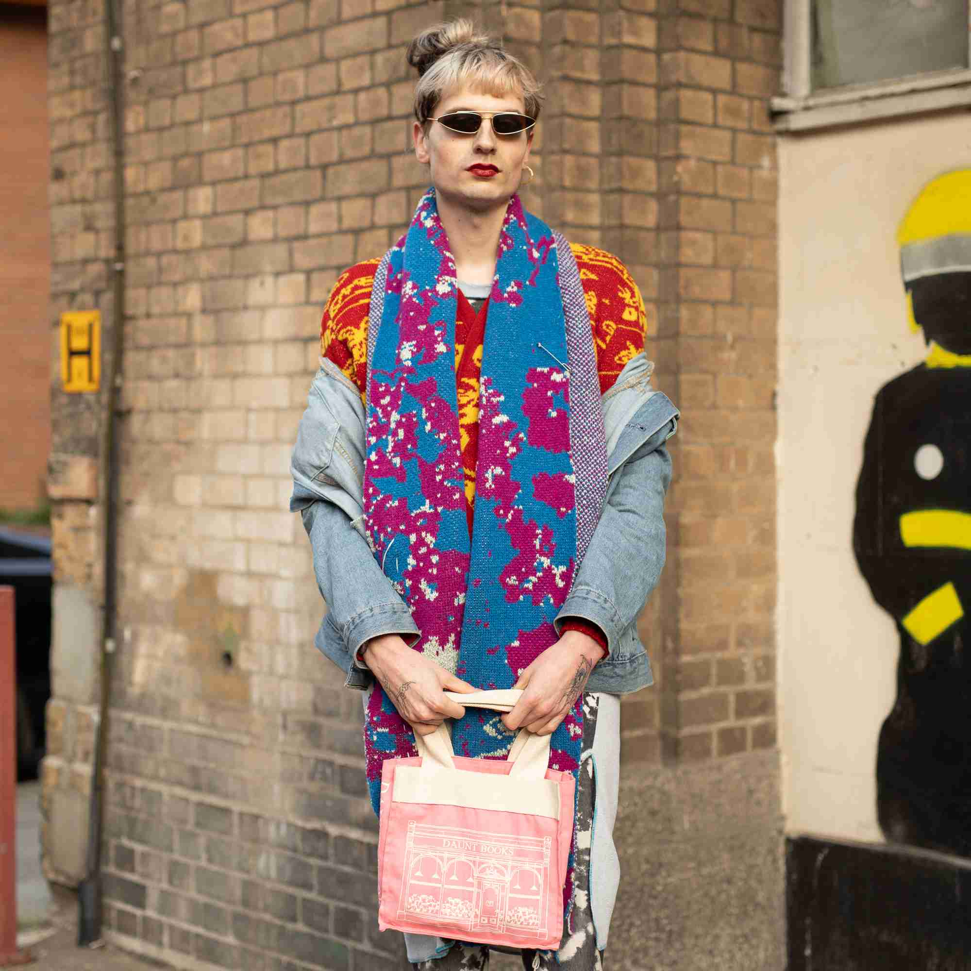 Street style fashion woman in jean jacket and floral scarf and flowered pants