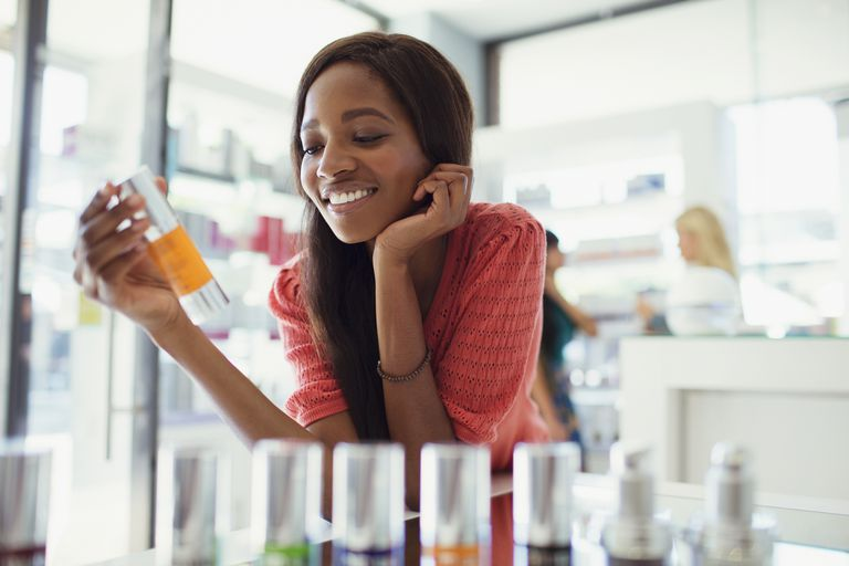 Woman examining skin care product in drugstore