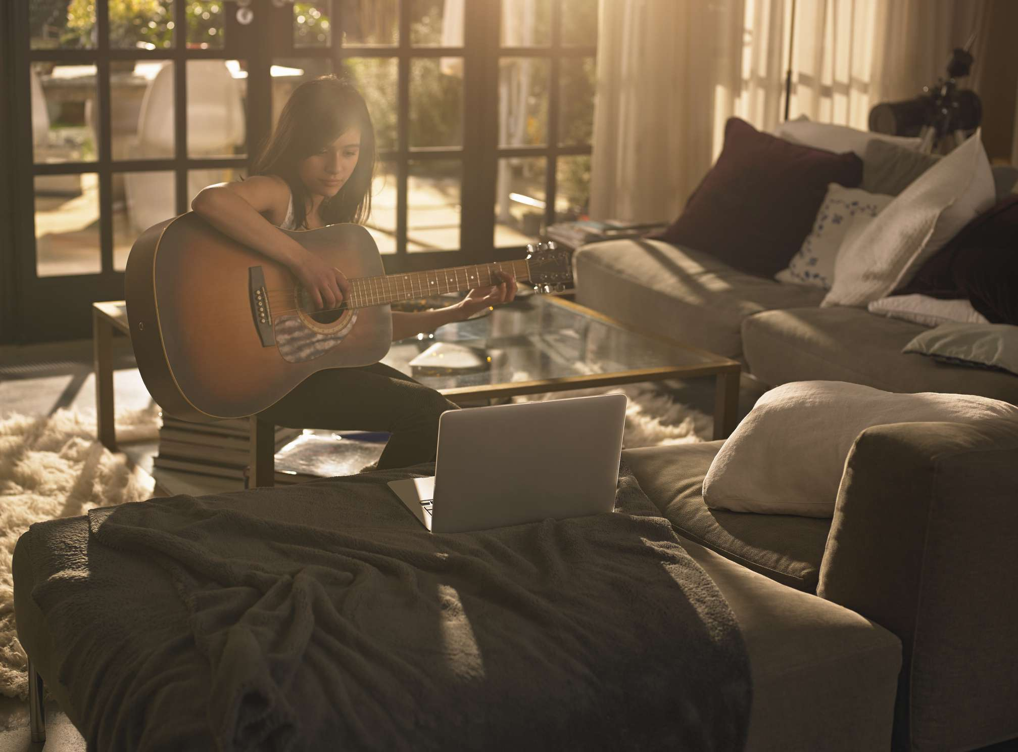girl playing guitar in living room