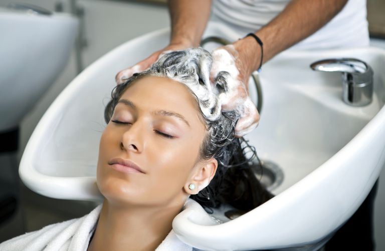 Hairstylist shampooing woman's thin hair with lightweight products
