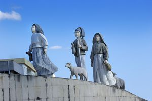 Statues of three children in biblical dress with two sheep atop a curved wall