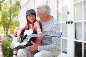 Older man and granddaughter playing guitar