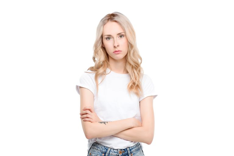 Blonde-haired woman wearing white shirt with crossed arms looks annoyed