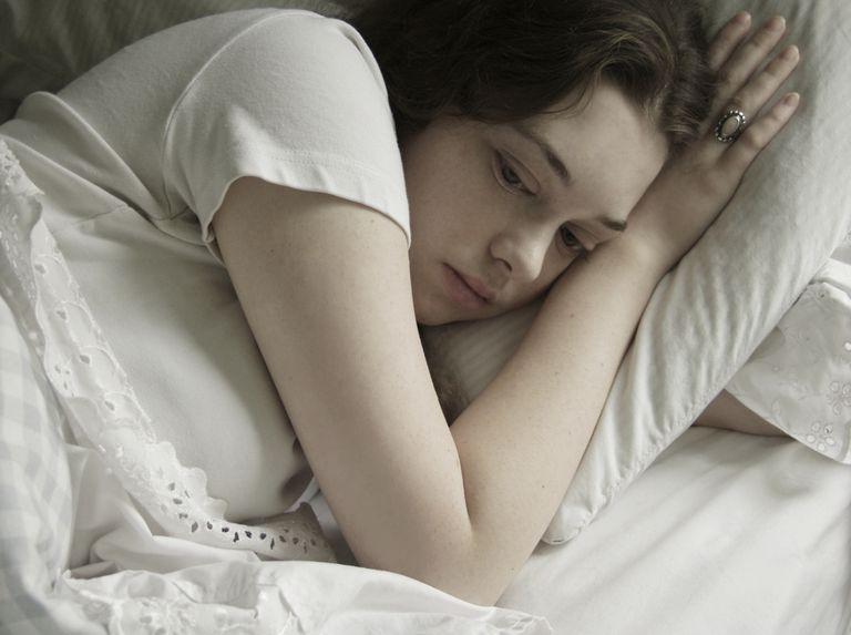 Sad teenage girl lying in bed