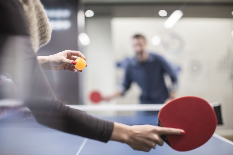 05f2ef030 Two colleagues playing table tennis in office break room