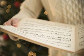 A woman holding Christmas sheet music.