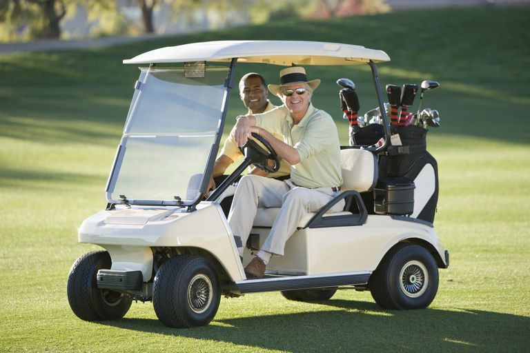 Two golfers riding in a golf cart.