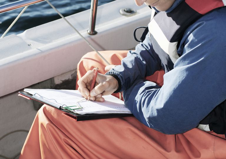 High angle view of woman examining while writing on clipboard in boat