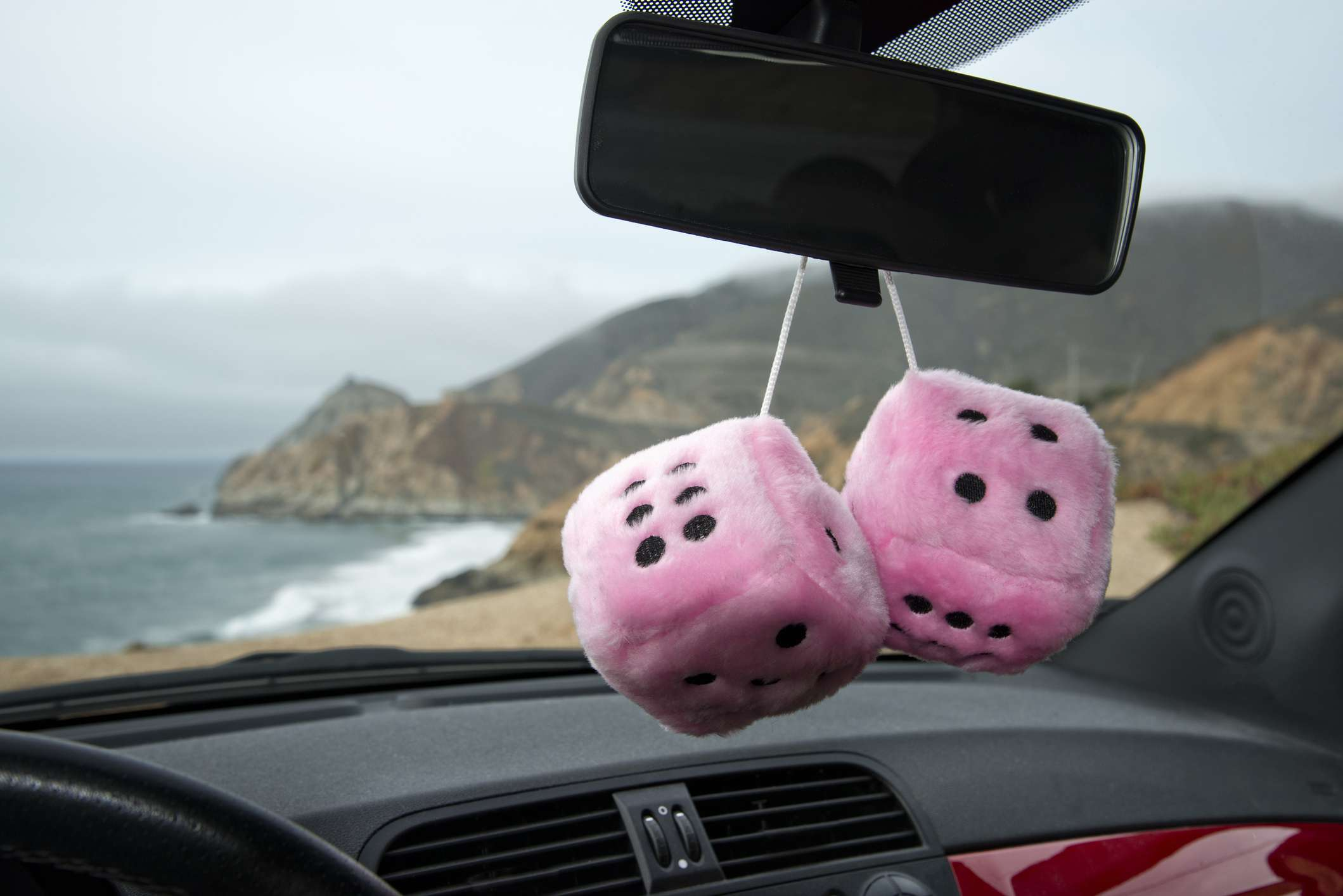 Pink fuzzy dice hanging from the rear-view mirror of a car