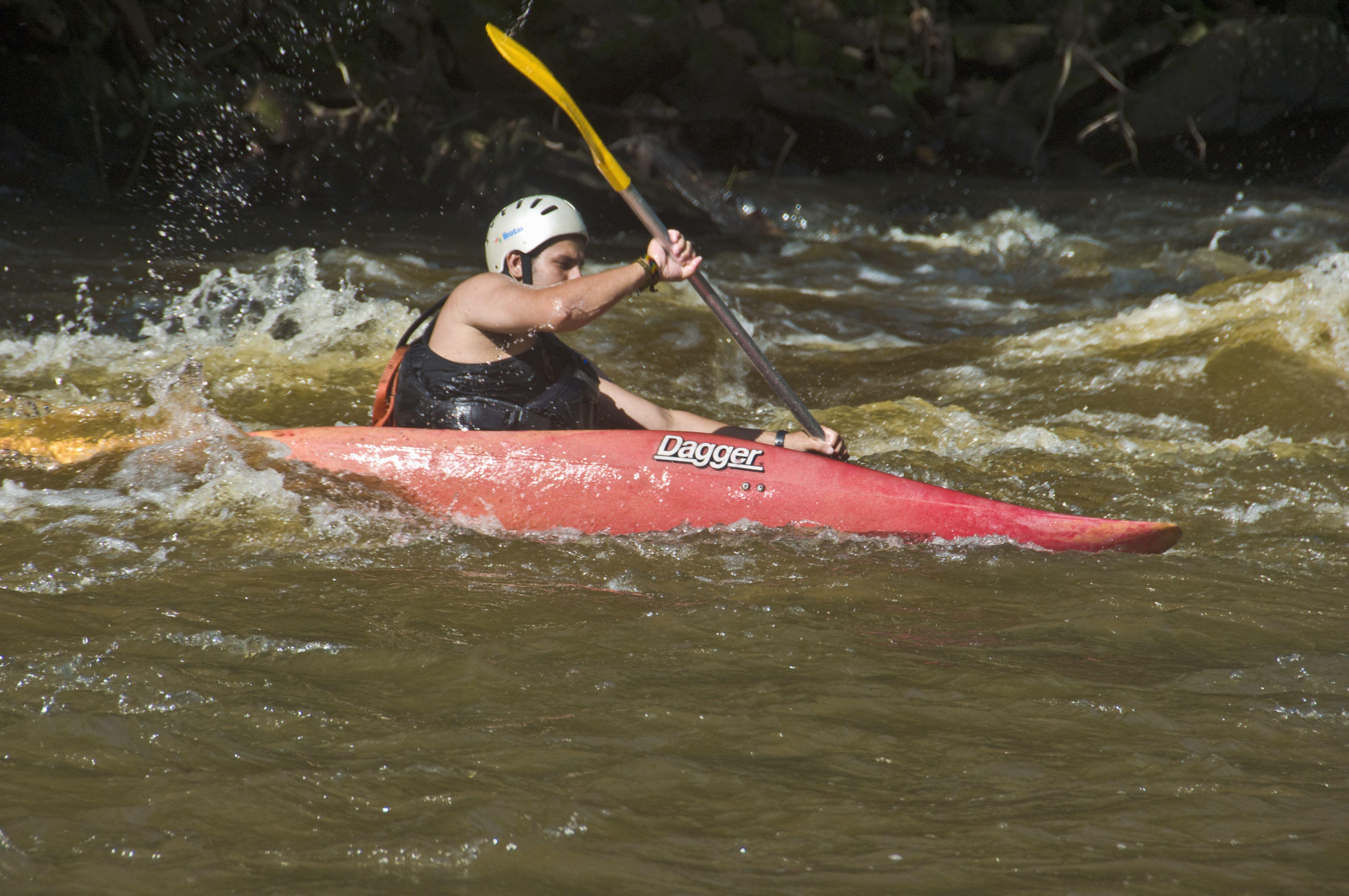 Canoeist in red Dagger kayak negotiates rapids.