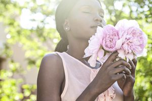 Woman breathing scent of flowers outdoors