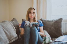 Young woman sitting on a couch reading manga in the daytime.