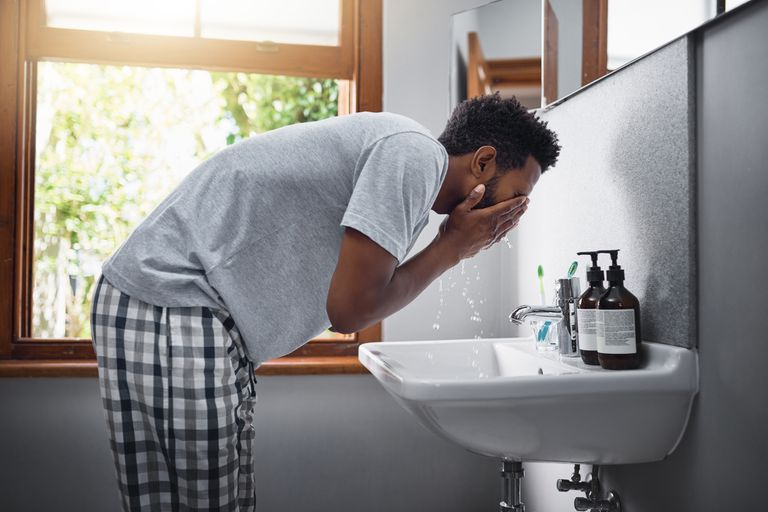 Man washing his face in bathroom sink