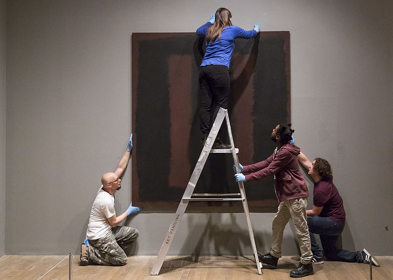 Art handlers hanging a Mark Rothko painting that has been restored.