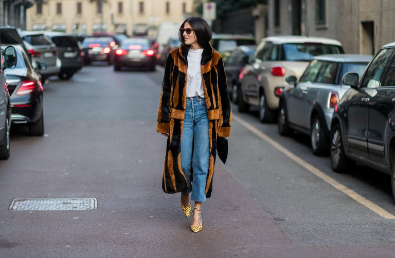 Street style woman in t-shirt and jeans and faux fur coat