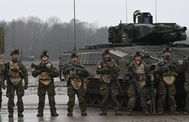 US Army soldiers standing in front of tank in Germany