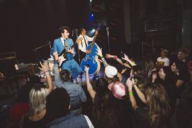 Crowd cheering for rockabilly musicians performing on stage at music concert